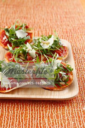 Rocket lettuce and confit tomato mini pizzas