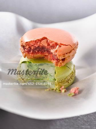 Half eaten rose-flavored and pistachio macaroons