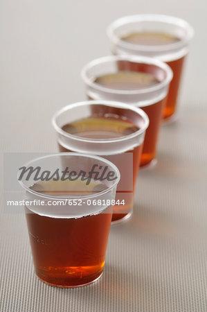 Row of plastic glasses of tea