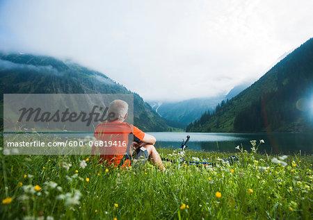 Mature Man with Mountain Bike sitting by Lake, Vilsalpsee, Tannheim Valley, Tyrol, Austria