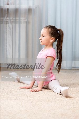 Ballerina girl doing the splits in her bedroom