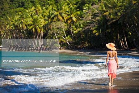 Dominica, Calibishie. A young woman walks along Batibou Beach. (MR).