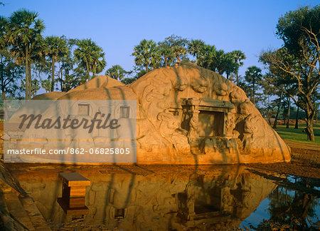 Asia, India, Tamil Nadu. Mahabalipuram (Mamallapuram).  Excavated temple at Saluvankuppam with the Tiger cave mandapa with carvings of tigers' heads.    At sunrise.