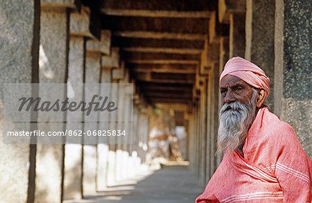 Asia, India, Karnataka, Hampi, Hampi bazaar.  Old pillgrim man seated in the shade of the Sule bazaar.