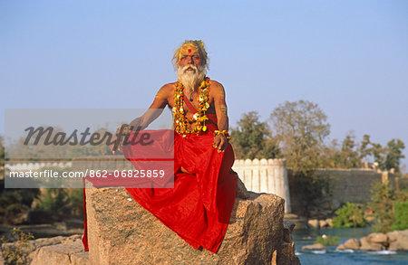 Asia, India, Madhya Pradesh, Orchha.   A Sadhu sits on a rock beside the Betwa River.