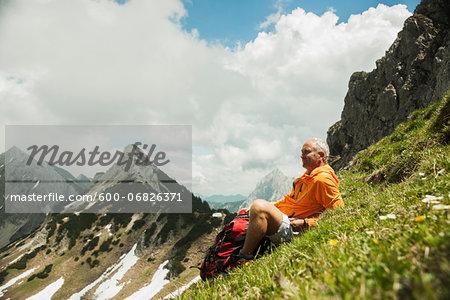 Mature man sitting on grass, hiking in mountains, Tannheim Valley, Austria