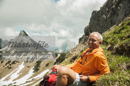Portrait of mature man sitting on grass, hiking in mountains, Tannheim Valley, Austria