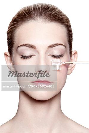 Close-Up of Woman with Eyes Closed Brushing Eyelashes