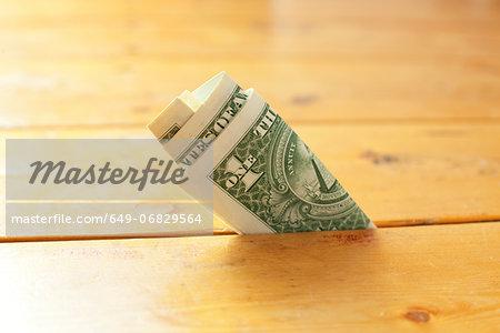 One dollar bill in between floorboards