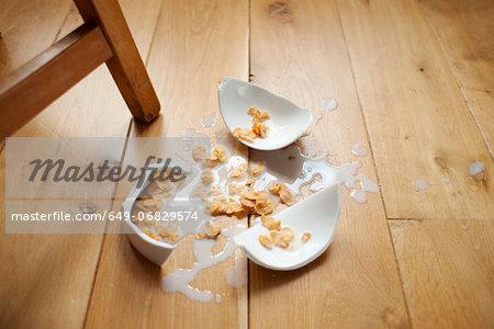 Broken bowl of cereal on wooden floor