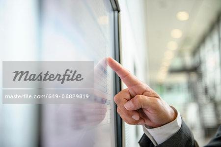 Close up of hand pointing at wall screen