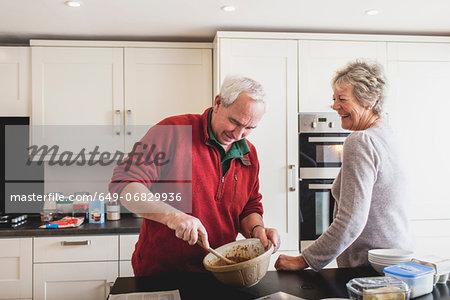 Senior couple baking in kitchen