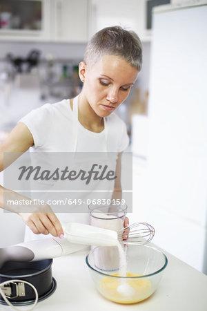Woman pouring sugar into mixing bowl