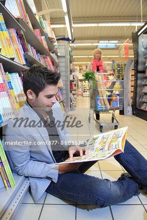 France, supermarket. Reading man.