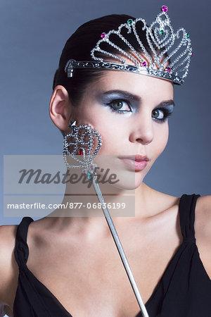 Young woman holding fairy wand, tiara, black dress