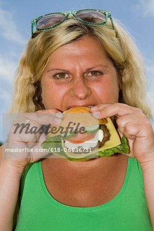 Mature woman enjoying burger outdoors