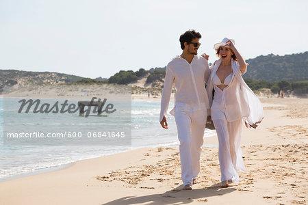 Young couple walking at the beach during summer holidays, Sardinia, Italy