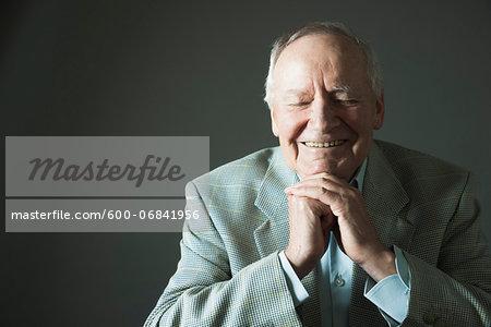 Portrait of senior man smiling with eyes closed, studio shot on grey background