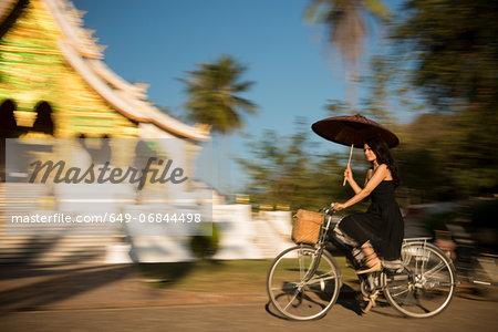 Woman riding bicycle with parasol, Luang Prabang, Laos