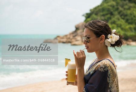 Woman drinking on beach, Banyon Tree Resort, Ko Samui, Thailand