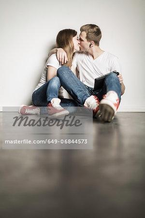 Teenage couple sitting on floor kissing