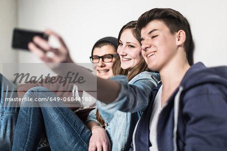 Three teenagers taking self portrait photograph using smartphone