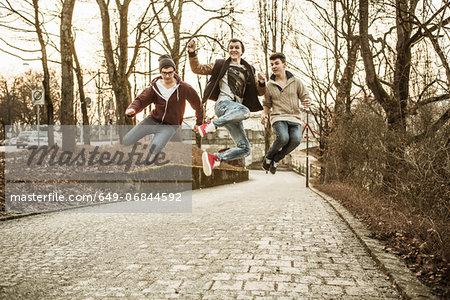 Three teenage boys jumping in park