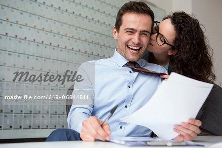 Woman kissing businessman's ear