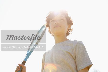 Boy holding up tennis racket