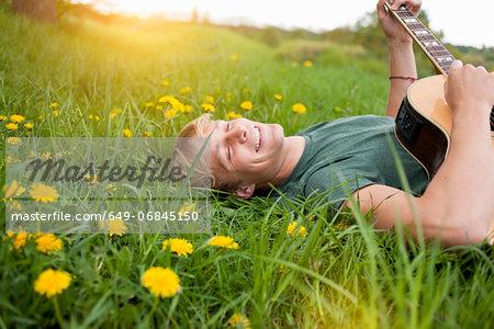 Young man lying in grass playing guitar