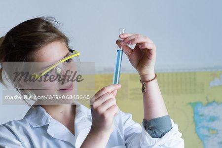 Close up of teenage girl examining test tube