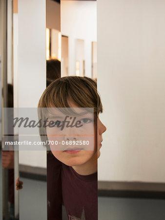 Boy Peeking Between Mirrored Pillars