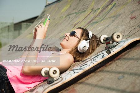 Teenage Girl Listening to MP3 Player in Skatepark, Feudenheim, Mannheim, Baden-Wurttemberg, Germany
