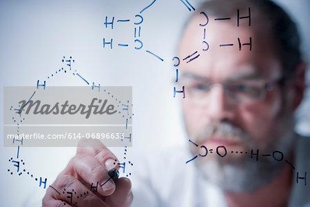 Scientist writing scientific symbols on glass