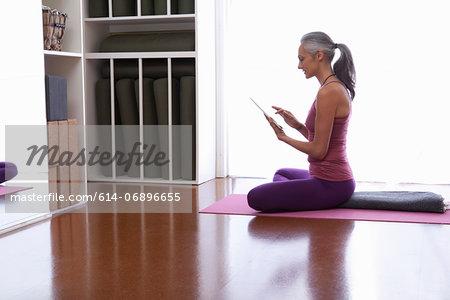 Woman using digital tablet sitting cross legged