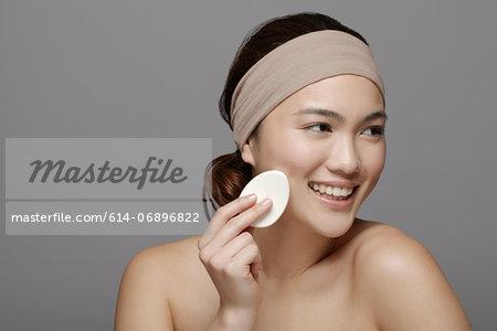 Young woman using make up sponge