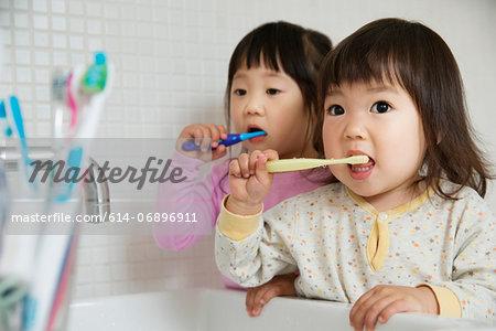 Two girl toddlers brushing teeth at bathroom sink