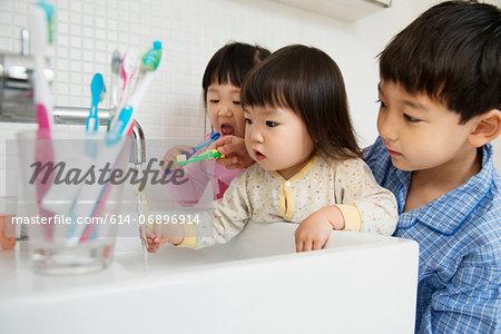 Brother helping sisters to clean teeth