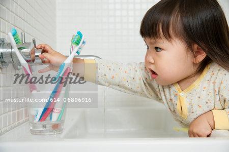 Close up of girl toddler turning bathroom sink taps