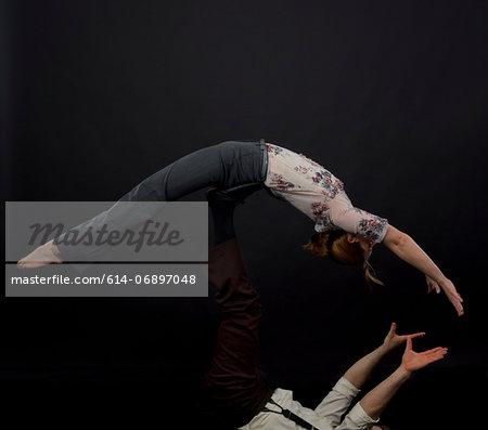 Studio shot of acrobats performing balancing trick