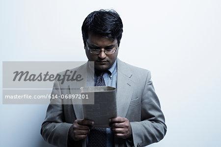 Studio portrait of businessman looking at newspaper