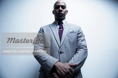 Studio portrait of businessman looking down at viewer