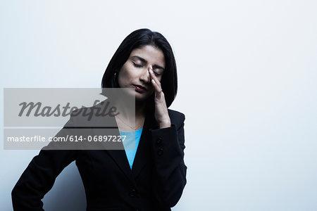 Studio portrait of businesswoman rubbing eyes