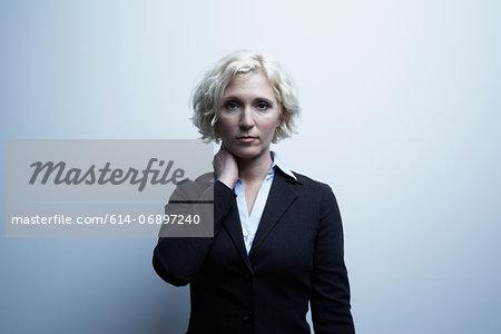 Studio portrait of businesswoman with hand on neck