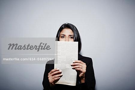 Studio portrait of businesswoman holding up newspaper