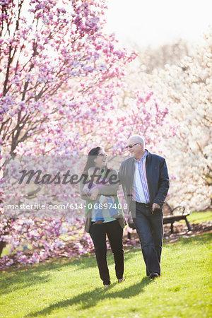 Grandparents and granddaughter walking in park