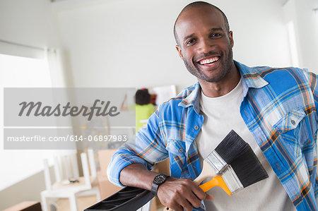 Mid adult man holding paintbrushes