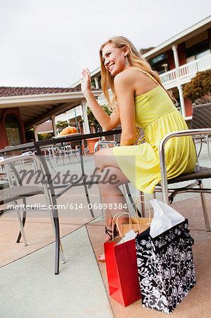 Woman shopper waving from café
