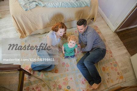 Couple lying on floor with child
