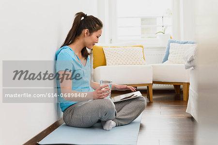 Woman sitting on mat using digital tablet